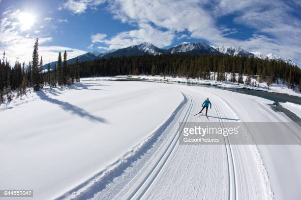A woman enjoys a cross-country skate ski next to a river in British Columbia, Canada.