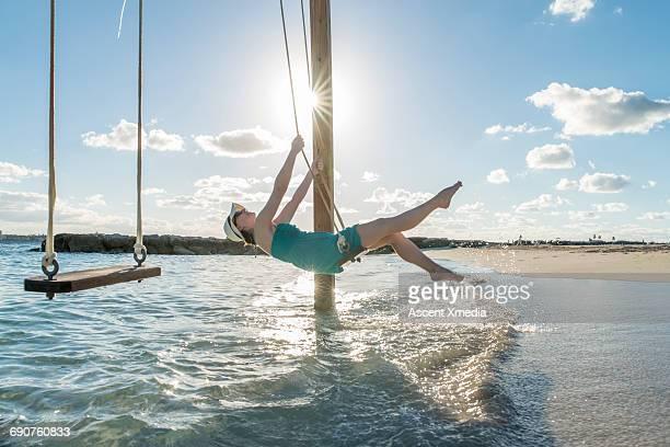 Woman enjoys beach swing above sea shallows