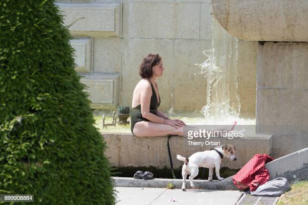 A woman enjoys cooling down in the water of the fountain of the Trocadero next to the Eiffel Tower during the heat wave on June 22 2017 in Paris...