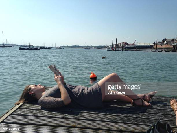 A woman enjoys reading a book by the water in Burnham on Crouch in Essex