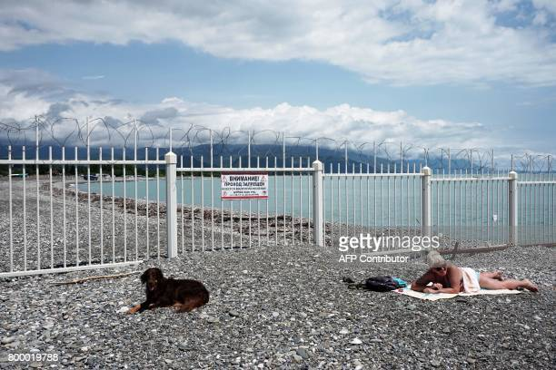 A woman enjoys the sun on the beach at the Black Sea by the fence on the border between Russia and Georgia's breakaway region of Abkhazia during the...