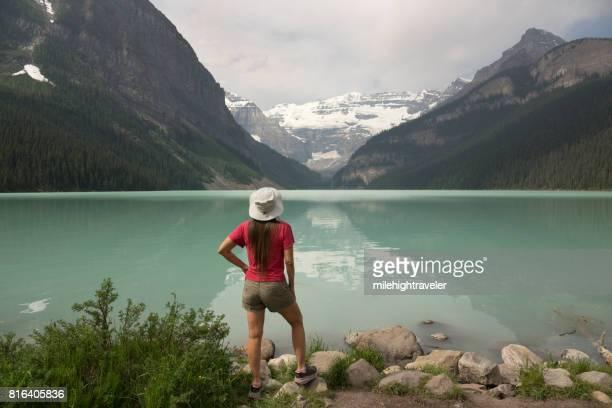 Woman enjoys turquoise Lake Louise waters Mount Victoria Banff National Park