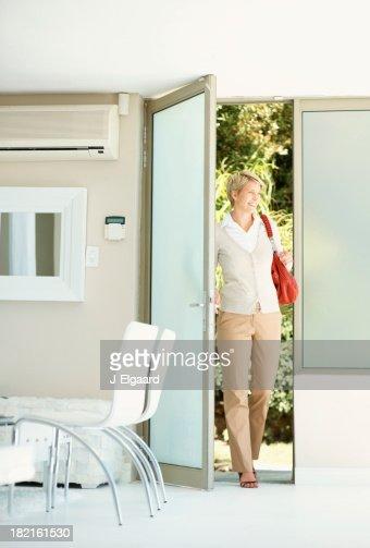 Femme entrant dans la maison à la porte