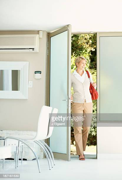 Woman entering her house through the door