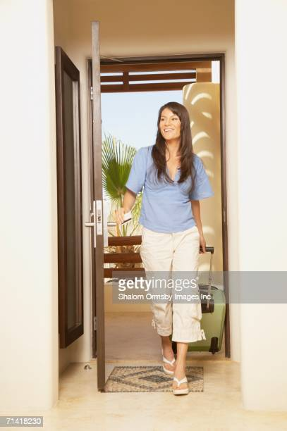 Woman entering hotel room with suitcase