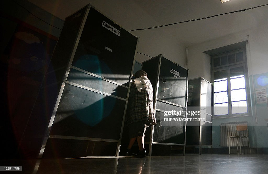 A woman enters a voting booth in a polling station in Rome on February 24, 2013, as part of Italy's general elections. Italians fed up with austerity voted in the country's most important election in a generation, as Europe held its breath for signs of fresh instability in the eurozone's third economy. AFP PHOTO / FILIPPO MONTEFORTE