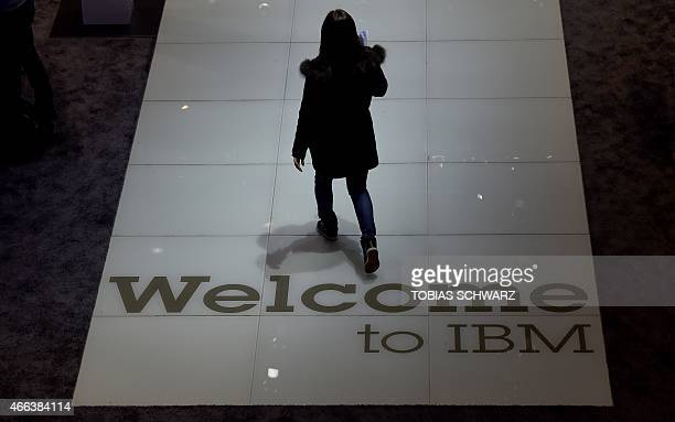 A woman enters the boot of IBM at the CeBIT technology fair in Hanover on March 15 2015 The CeBIt runs from March 16 till 20 AFP PHOTO / TOBIAS...