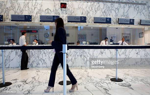 A woman enters the line to speak to a teller at a Grupo Financiero Inbursa SAB bank branch in Mexico City Mexico on Tuesday June 25 2013 CaixaBank SA...
