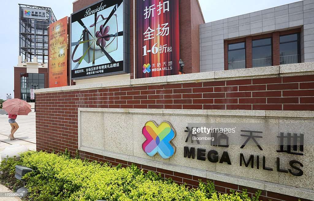A woman enters the Mega Mills shopping mall, operated by The Outlet! Company, in Shanghai, China, on Tuesday, July 2, 2013. Banks including Goldman Sachs Group Inc. have pared their growth projections for China this year to 7.4 percent, below the government's 7.5 percent goal disclosed at the March conference at which Li Keqiang became premier. Photographer: Tomohiro Ohsumi/Bloomberg via Getty Images