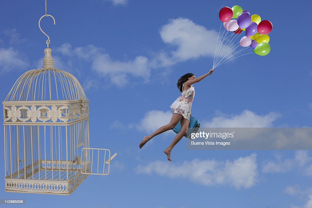 Woman escaping from a cage with balloons : Stock Photo