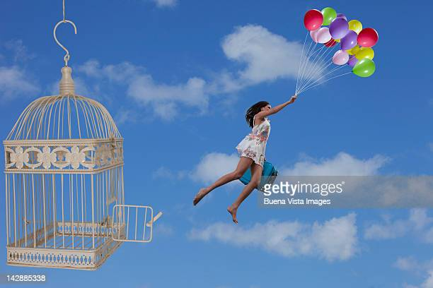 Woman escaping from a cage with balloons