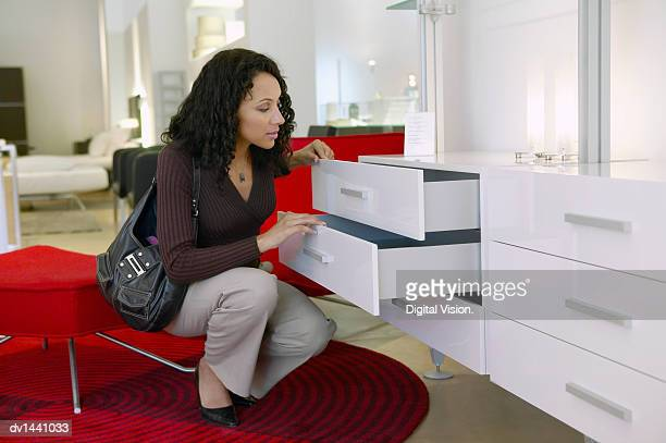 Woman Examines a Chest of Drawers in an Interiors Shop