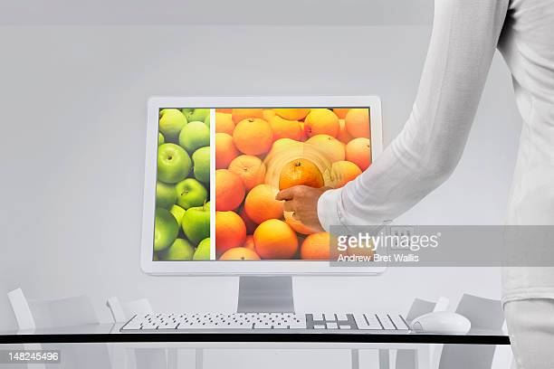 Woman examines an orange through a desktop screen
