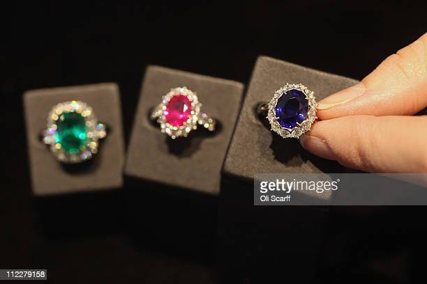 A woman examines emerald ruby and sapphire rings set in the Garrard Royal Cluster in Garrard's flagship store in Mayfair on April 6 2011 in London...
