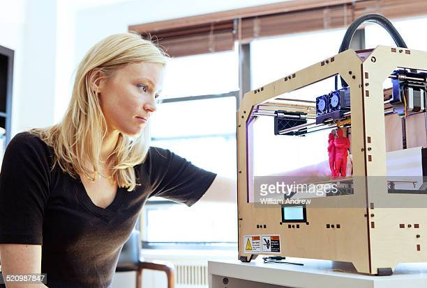 Woman examines print from 3D printer