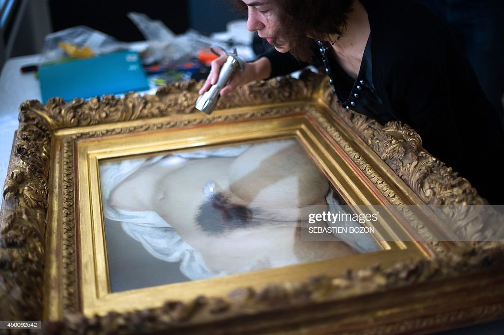 A woman examines the Gustave Courbet's canvas 'L'origine du monde' before its installation at the Courbet museum on June 3 in Ornans eastern France...