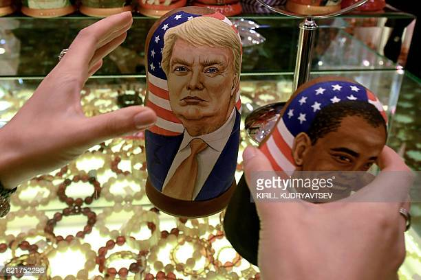A woman examines traditional Russian wooden nesting dolls Matryoshka dolls depicting US Republican presidential nominee Donald Trump and US President...