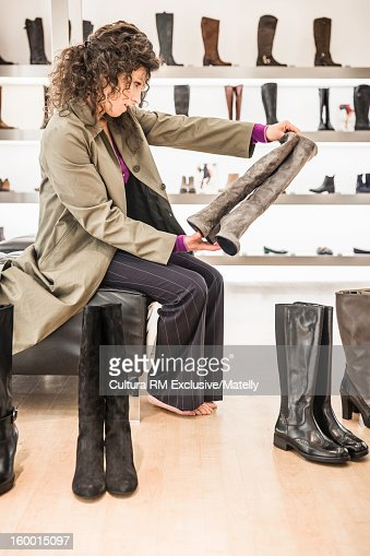 Woman examining boots in store : Stock Photo