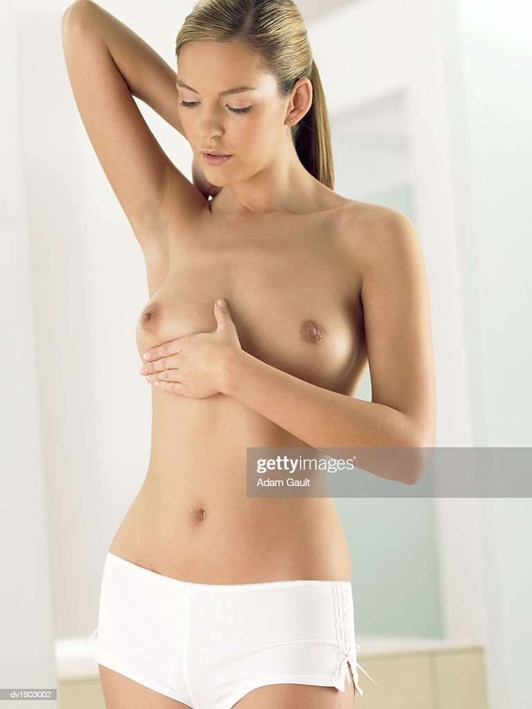 Woman Examining Her Breast in a Bathroom : Stock Photo