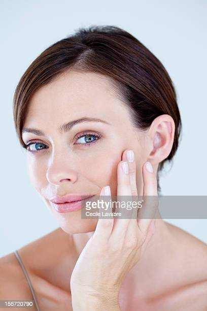 A woman examining her face with her finger