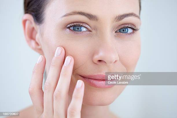 Woman examining her face with her fingers