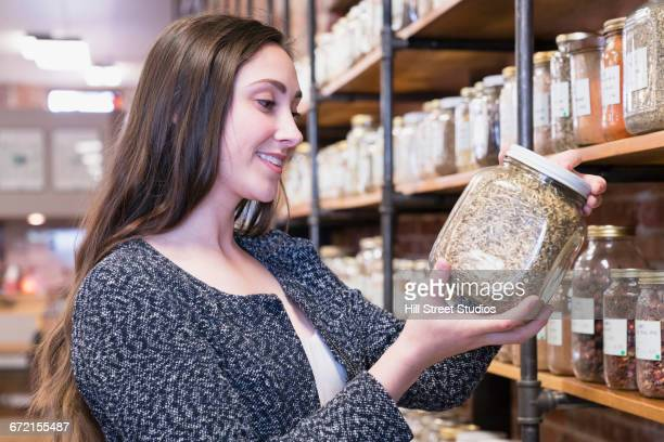 Woman examining jar in nutrition store