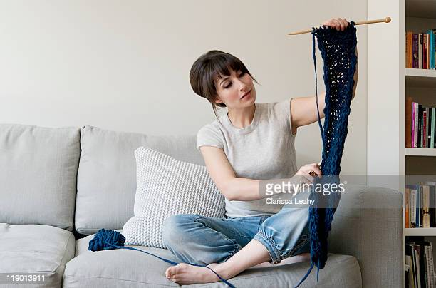 Woman examining knitting in living room
