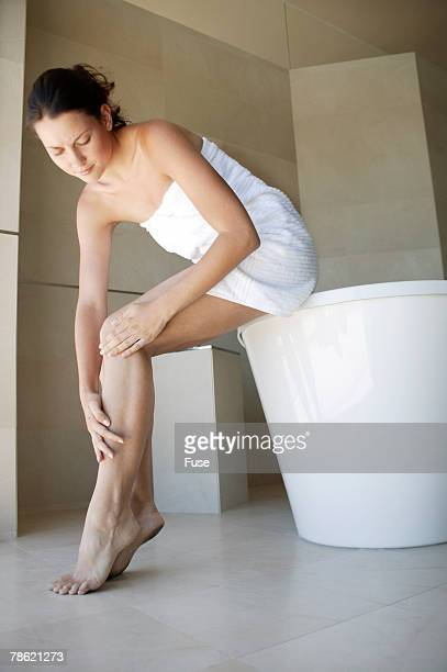 Woman Examining Leg in Bathroom