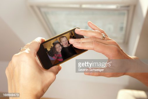 Woman examining picture on cell phone