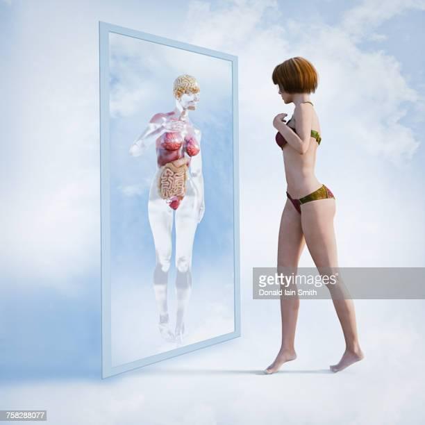 Woman examining reflection of organs in virtual mirror