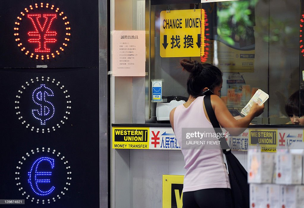 A woman exchanges money at a currency exchange shop in Hong Kong on September 15 2011 Hong Kong said it has no plans to unpeg its currency from the...