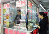 A woman exchanges money at a foreign exchange shop in the Wanchai district of Hong Kong 24 September 2003 Hong Kong Financial Secretary Henry Tang...