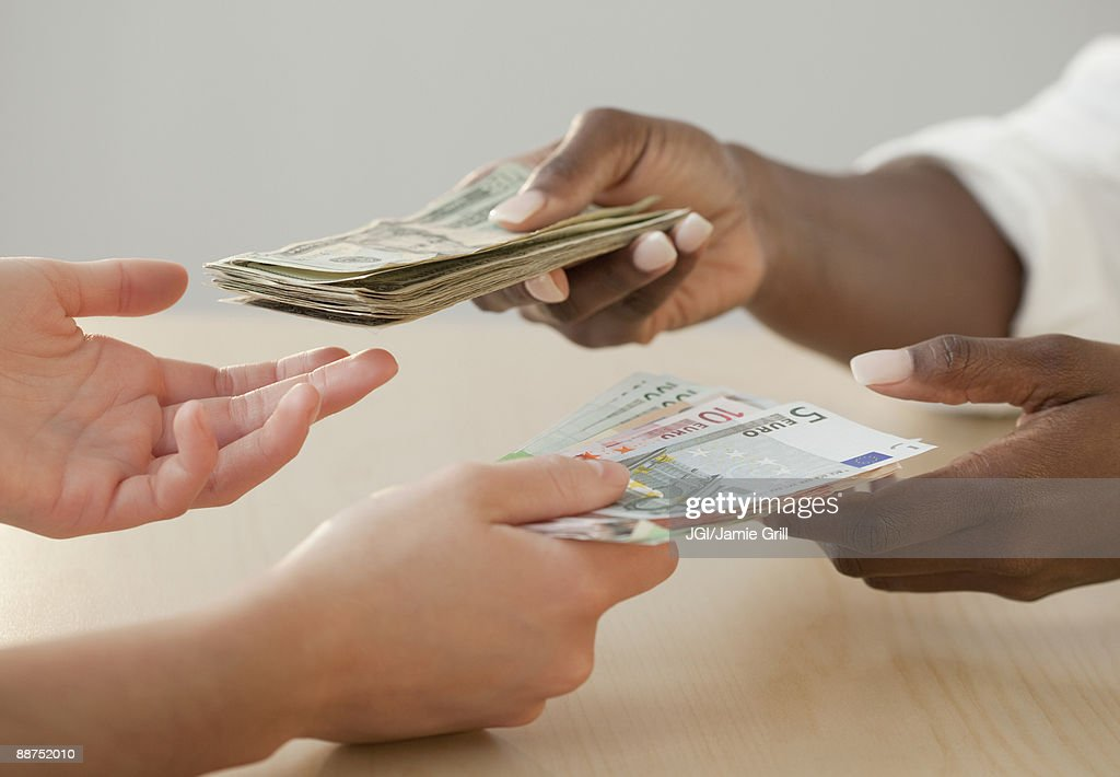 Woman exchanging Euro notes for US currency