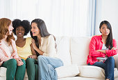 Woman excluded from conversation on sofa