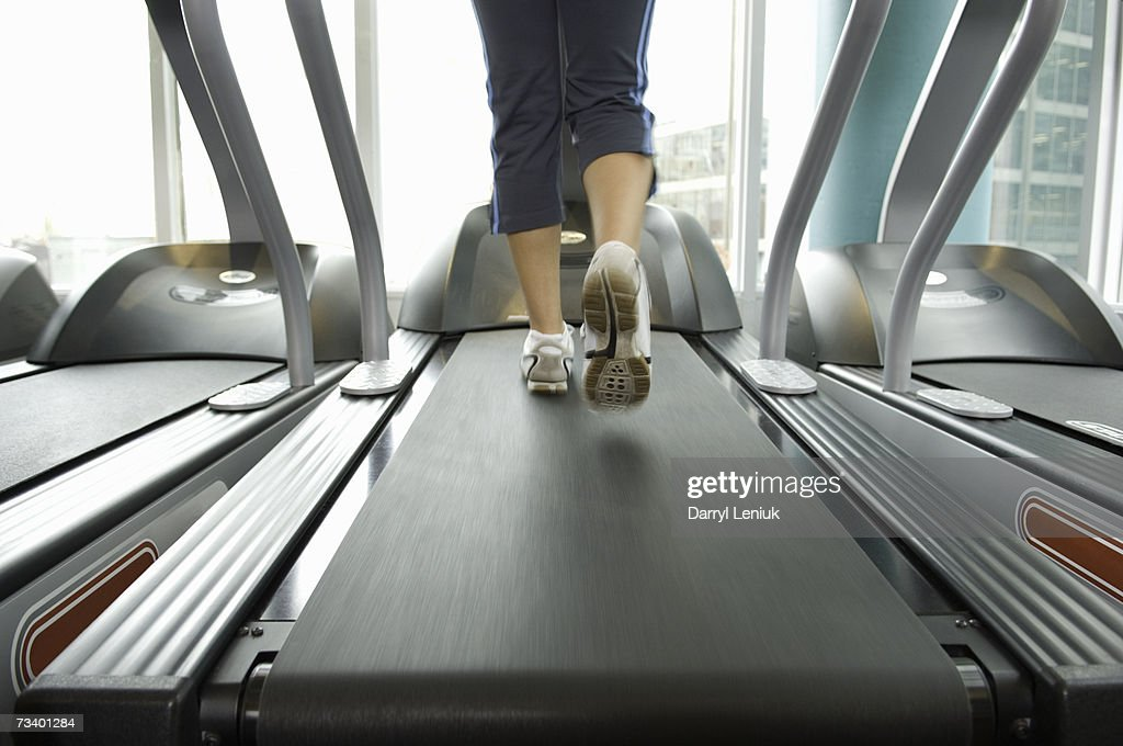 Woman excursing on treadmill, low section : Stock Photo