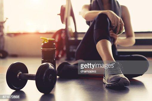 Entrainement exercice femme en rupture de fitness gym relax holding fruits pomme après le sport de formation avec des haltères et des protéines secouer bouteille culturisme de saines habitudes de vie. : Photo