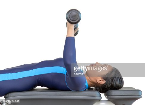 Woman exercises with dumbbells in the gym : Stock Photo