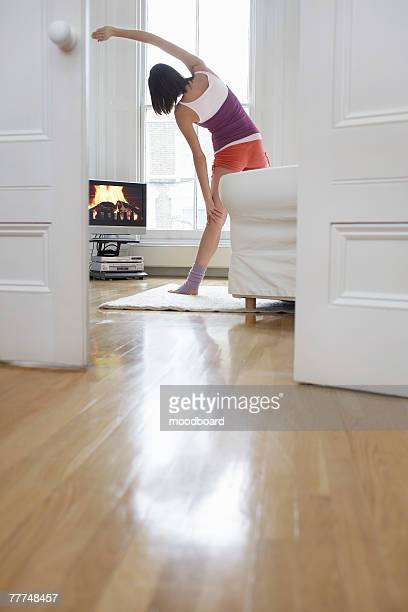 Woman Exercising and Watching Television in Living Room