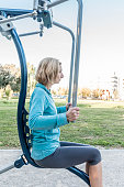 Woman Exercising at Fitness Equipment in a Park