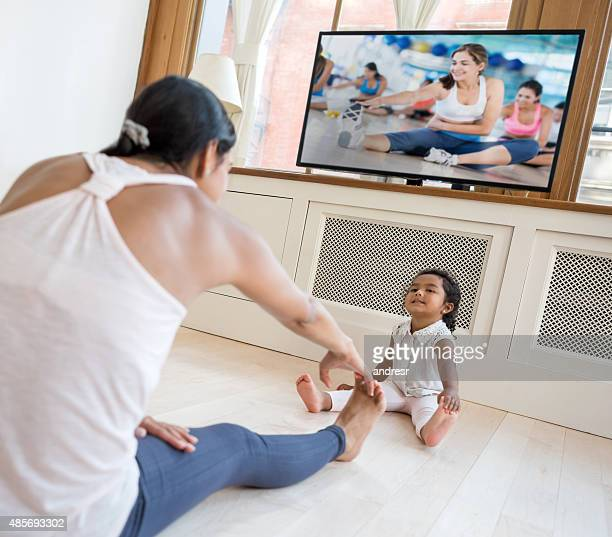 Woman exercising at home and watching the baby