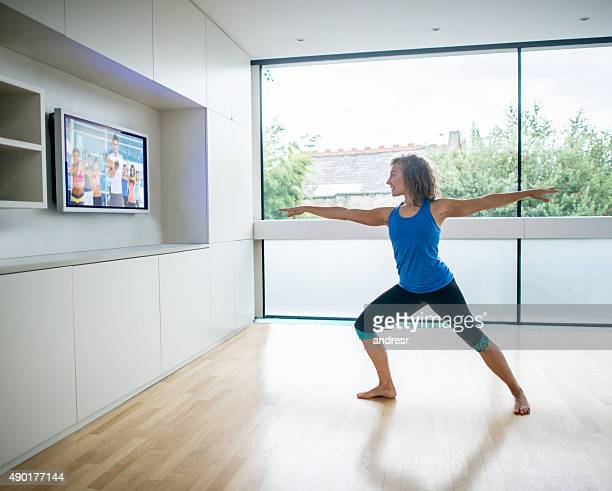 Woman exercising at home watching a Pilates DVD