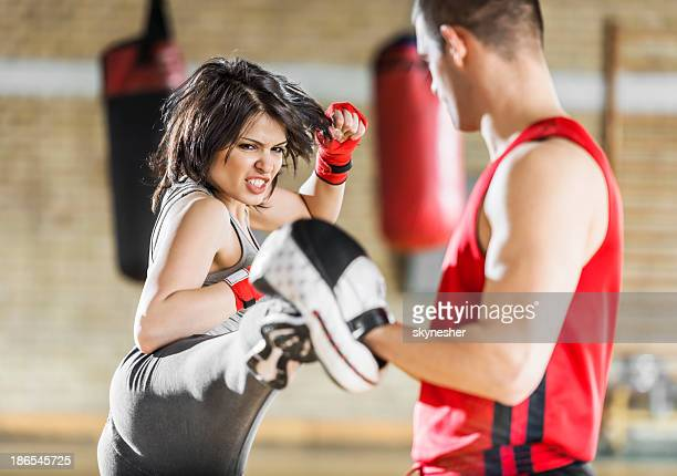 Woman exercising boxing in a gym.