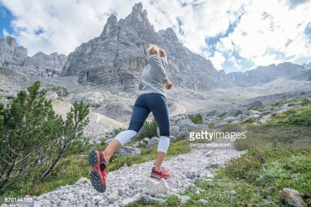 Woman exercising for cross-country running, dolomites, Italy