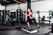 Young sportive woman exercising in gym using step platform