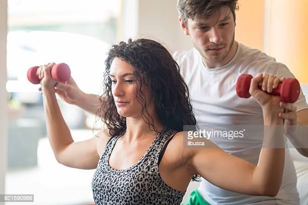 Frau Ausübung im Wohnzimmer mit persönlichem trainer