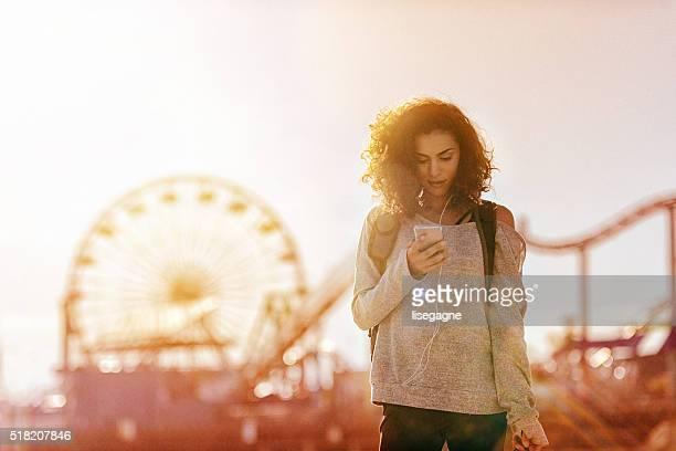 Woman exercising in LA, using smartphone, California