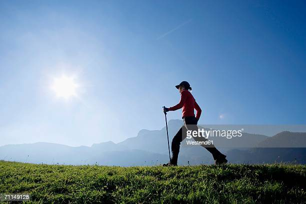 Austria, Alps, Woman holding ski pole walking, side view