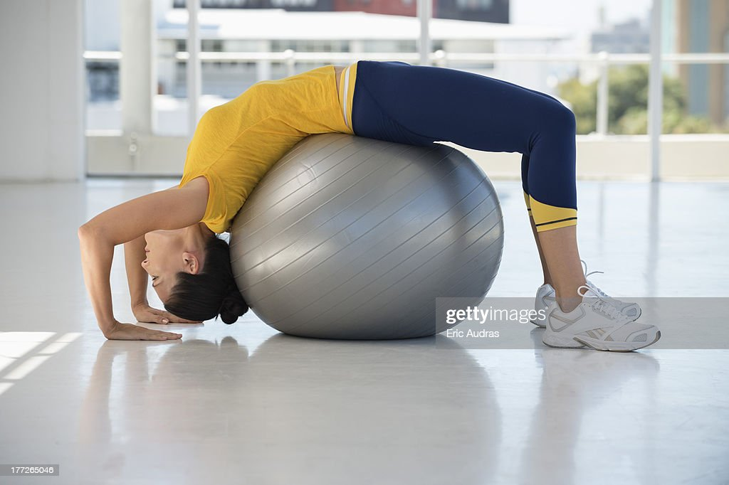 Woman exercising on a fitness ball in a gym