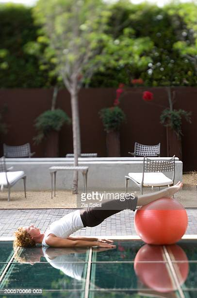 Woman exercising on fitness ball, side view