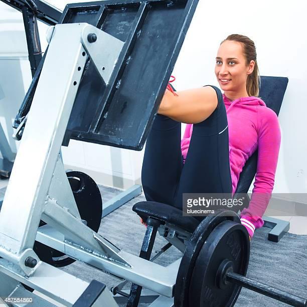 Woman exercising on leg press in gym